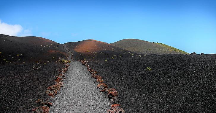 gray road between grass field near mountain
