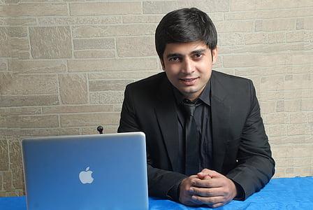 man sitting on chair beside silver MacBook