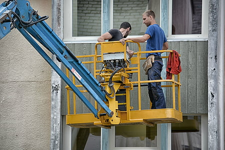 two men riding yellow power equipment
