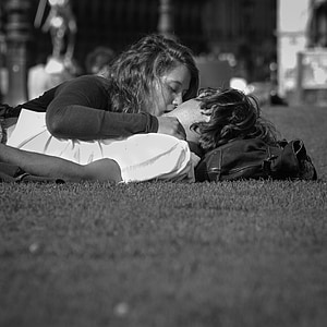 grayscale photo of man and woman kissing on field of grass