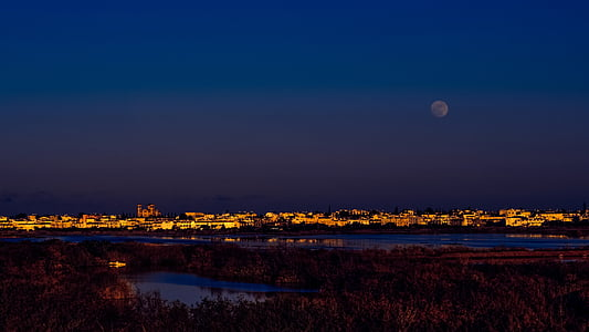 lighted city with full moon