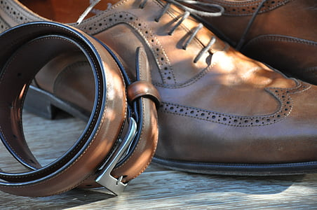 brown leather belt beside derby shoes