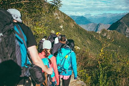 people trekking on mountain during daytime