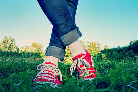 person wearing red sneakers in the grass field