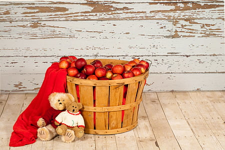 two brown bear plush toys leaning on brown wooden basket with red apple fruit lot