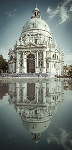 white concrete dome structure with reflection on water