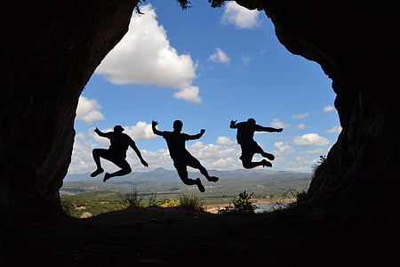 silhouette photo of three person hopping