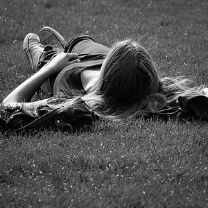 grayscale photo of woman lying on grass