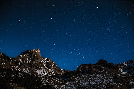 snow capped mountains under the starry skies