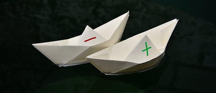 two white paper boats on body of water