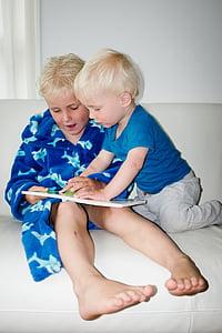boy holding white booki sitting on white sofa