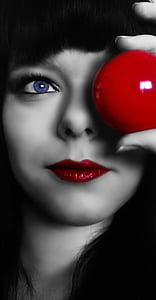 woman holding red ball in color selective photography