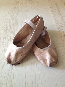 pair of pink leather ballet flats on wooden surface