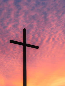 silhouette of cross taking photo during golden hour
