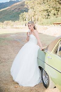 woman in white wedding dress sitting on car tailgate