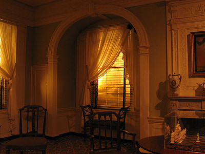 brown wooden chair beside window