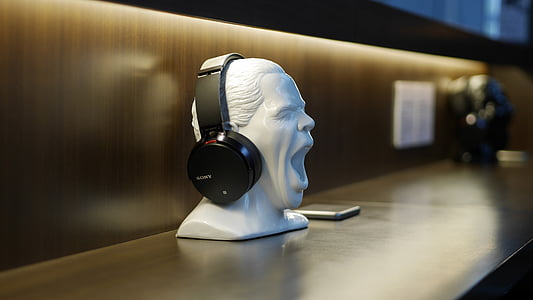 black wireless headphones on white person's head figurine