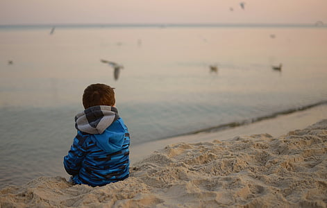 toddler sitting on sand beside body of water during daytime