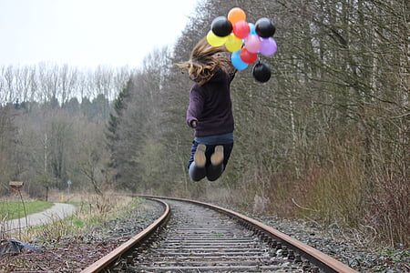 girl jumping on train track while holding balloons