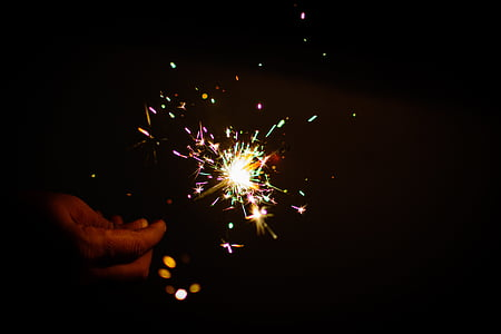 person holdiing multicolored sparkler