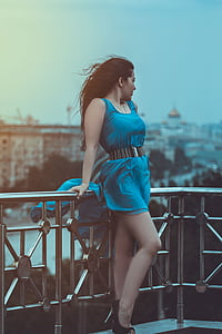 woman wearing blue scoop-neck sleeveless mini dress leaning on terrace while looking left