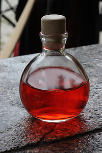 close-up photo of clear glass bottle with red liquid