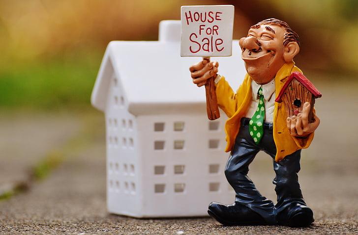 ceramic man holding house for sale figurine