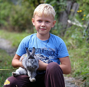 boy carrying gray rabbit