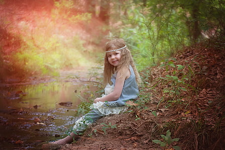 girl sitting on soil near body of water