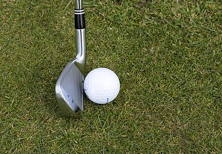 golf wedge beside golf ball