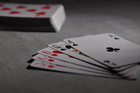selective focus photography of playing cards on gray textile