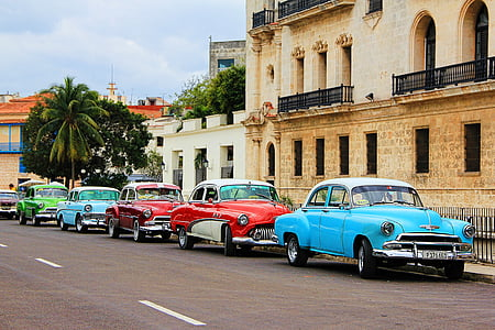 assorted-colored classic cars park on road beside black metal rails