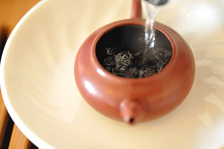 water poured in brown teapot