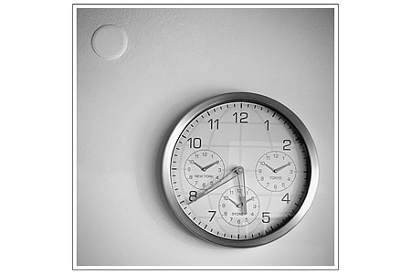 round grey metal chronograph wall clock displaying 5:39