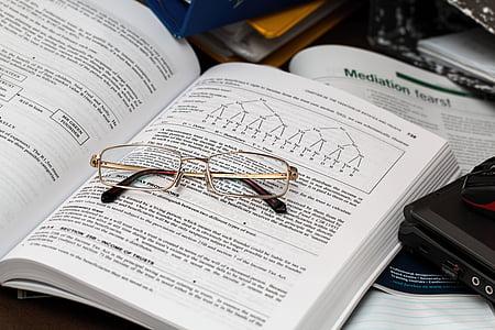 gold-colored framed eyeglasses on top of book