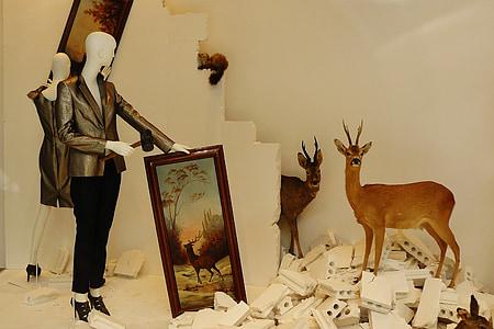 two brown deer taxidermies beside brown deer painting