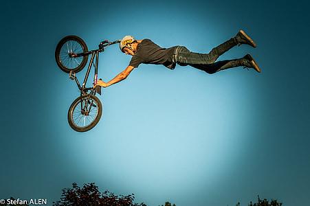man holding BMX bike making stunt