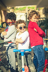 three boy standing in front of their bicycles and scooters