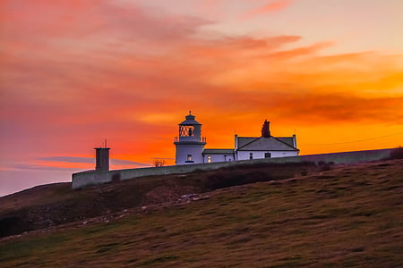 lighthouse under sunset sky