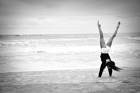 grayscale photo of doing flip on seashore