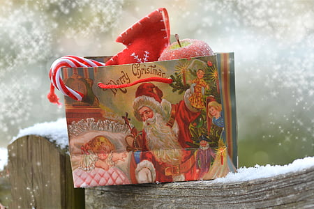 Merry Christmas-theme paper bag on grey wooden snow covered bar