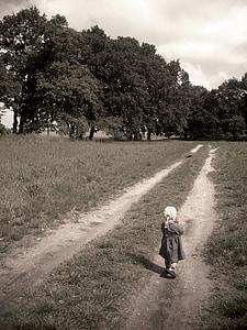 child walking toward forest