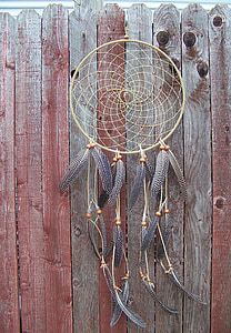 brown and gray dreamcatcher hanged on brown wooden fence