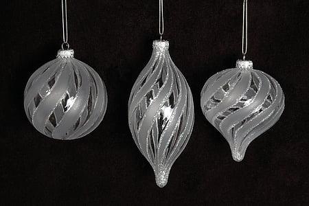 three gray baubles on dark background