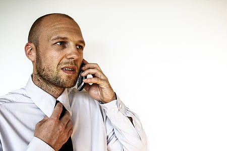 man holding his tie while talking to his phone