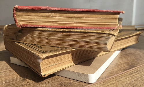 four assorted books on brown wooden surface