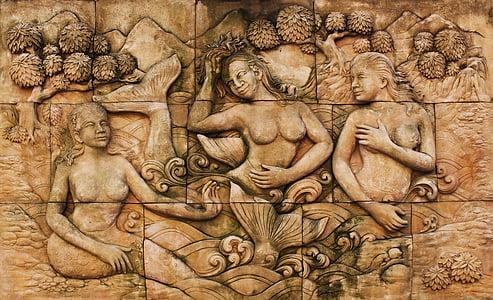 brown concrete wall with mermaid embossed art