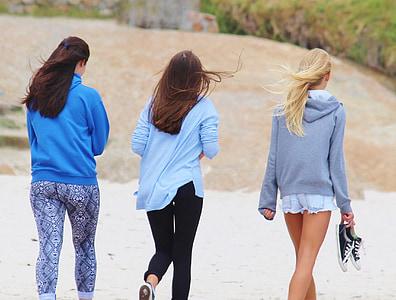 three women walking on seashore during daytime