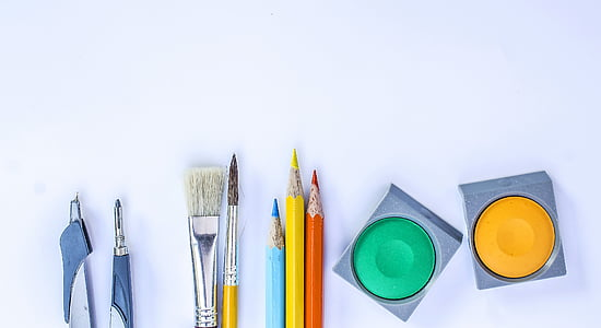 assorted art materials on top of white surface