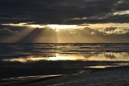 landscape photo of crepuscular light with body of water